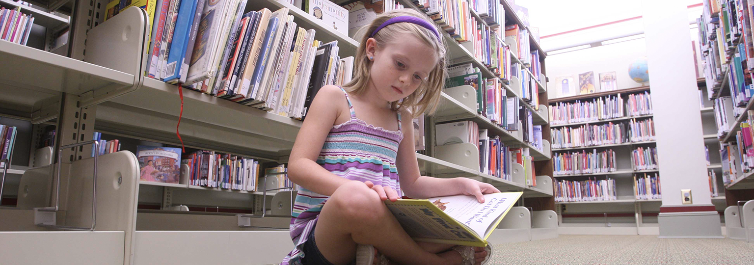 Young Girl Reading in Stacks