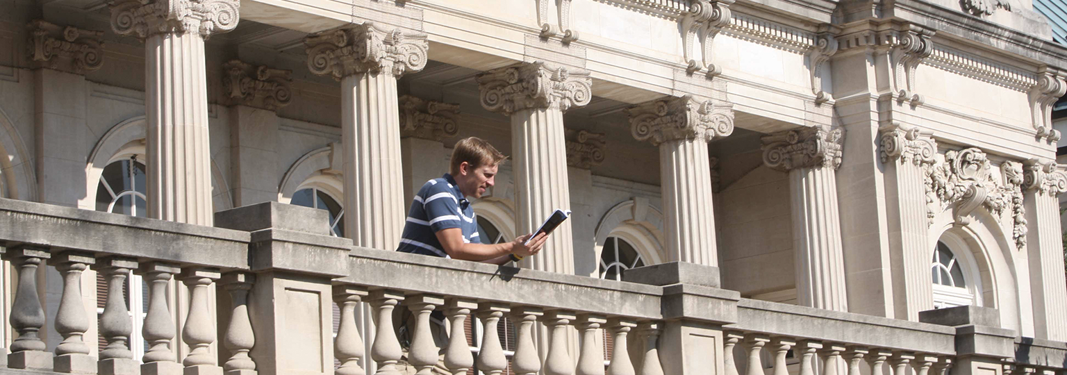 Man reading on the Handley Library Building Balcony